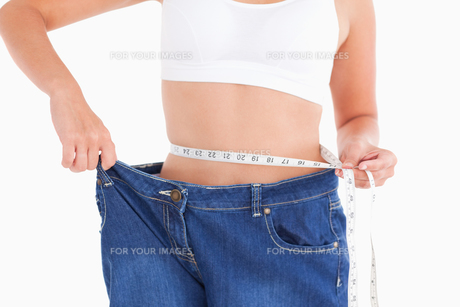Woman measuring her waist while wearing too big jeansの写真素材 [FYI00484596]
