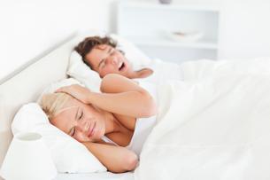 Annoyed woman awaken by her boyfriends snoringの写真素材 [FYI00484623]