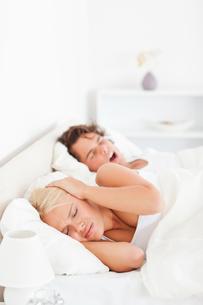 Portrait of an annoyed woman awaken by her boyfriends snoringの写真素材 [FYI00484626]