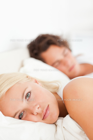 Portrait of a woman looking at the camera while her fiance is sleepingの写真素材 [FYI00484632]