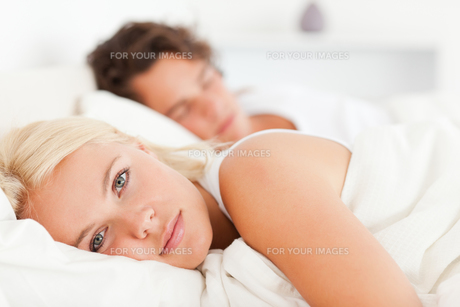 Woman looking at the camera while her fiance is sleepingの写真素材 [FYI00484633]