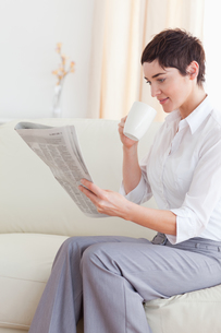 Portrait of a woman drinking coffee while reading the newsの素材 [FYI00484643]