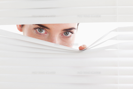 Brunette businesswoman peeking through a venetian blindの写真素材 [FYI00484647]