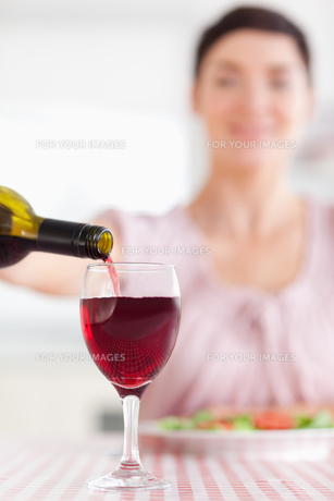 Brunette Woman pouring redwine in a glassの素材 [FYI00484649]