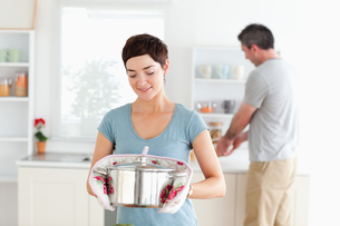 Cute Woman holding a pot while man is washing the dishesの写真素材 [FYI00484664]