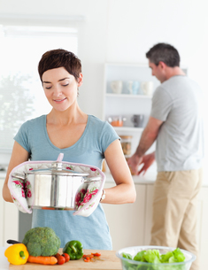 Cute wife holding a pot while her husband is washing the dishesの写真素材 [FYI00484666]