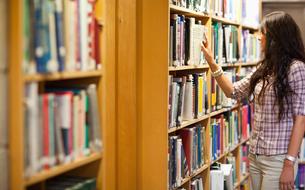 Young woman choosing a bookの写真素材 [FYI00484677]