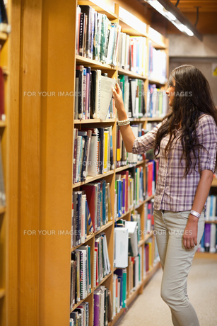 Portrait of a young woman choosing a bookの写真素材 [FYI00484679]