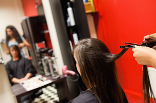 Cute woman having her hair straightenedの素材 [FYI00484702]