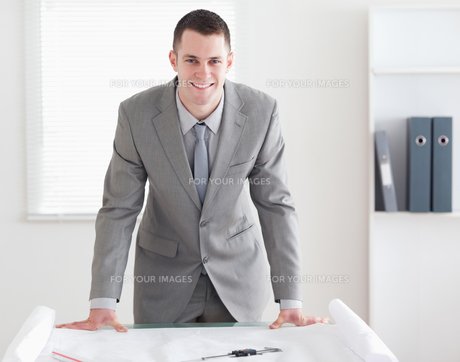 Smiling architect standing behind a tableの素材 [FYI00484704]