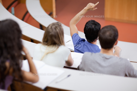 Young student raising his hand while his classmates are taking notesの写真素材 [FYI00484708]