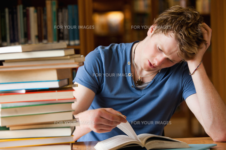 Tired man reading a bookの写真素材 [FYI00484714]