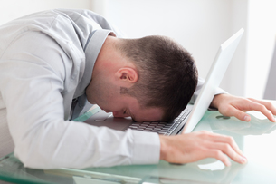 Close up of overworked businessman taking a nap on his laptopの写真素材 [FYI00484726]