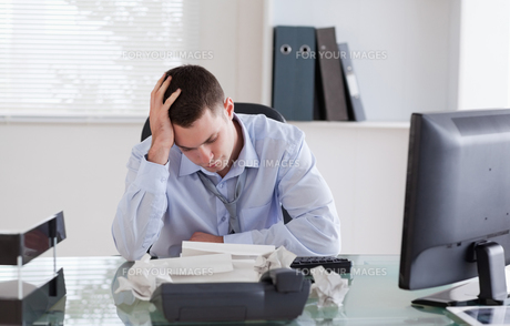 Businessman frustrated by paperworkの写真素材 [FYI00484733]