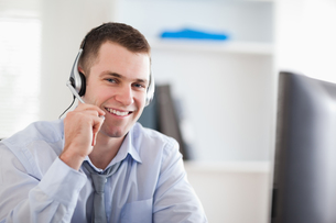 Smiling call center agent speaking with costumerの素材 [FYI00484740]