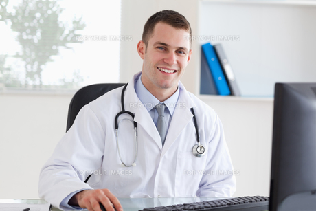 Smiling doctor on his computerの写真素材 [FYI00484742]