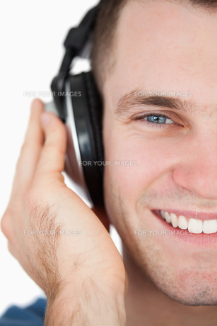 Close up of a smiling man listening to musicの写真素材 [FYI00484756]