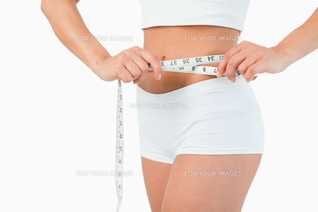 Feminine body with a measuring tapeの写真素材 [FYI00484776]