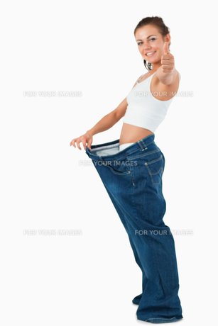 Portrait of a fit woman wearing too large pants with the thumb upの写真素材 [FYI00484785]