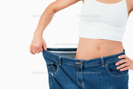 Fit woman wearing too large jeansの写真素材 [FYI00484792]
