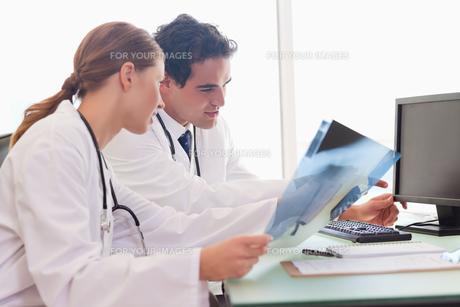 Medical team analyzing xraysの写真素材 [FYI00484807]