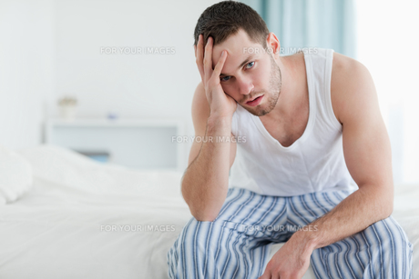 Depressed man sitting on his bedの写真素材 [FYI00484816]