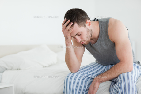 Exhausted man sitting on his bedの写真素材 [FYI00484817]