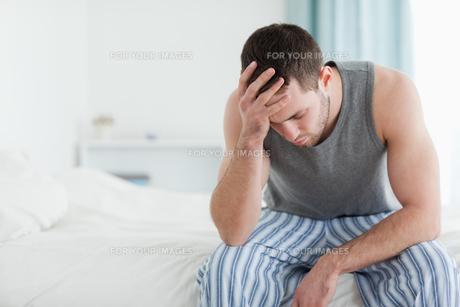 Sad man sitting on his bedの写真素材 [FYI00484820]