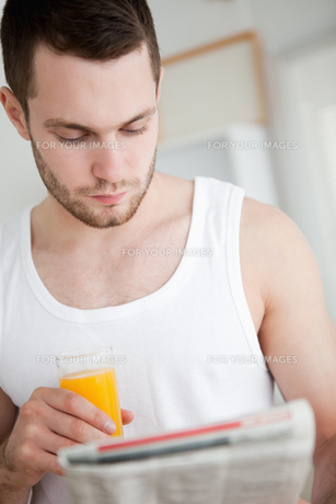 Portrait of a beautiful man drinking orange juice while reading the newsの素材 [FYI00484822]