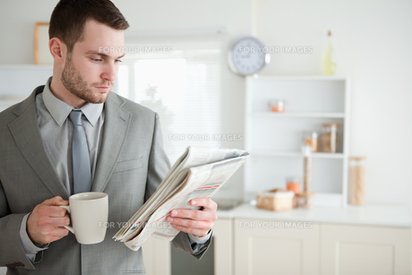 Businessman drinking coffee while reading the newsの素材 [FYI00484823]