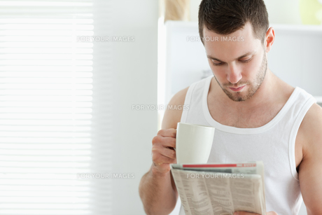 Smiling man drinking coffee while reading the newsの素材 [FYI00484824]