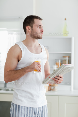 Portrait of a young man drinking orange juice while reading the newsの素材 [FYI00484825]