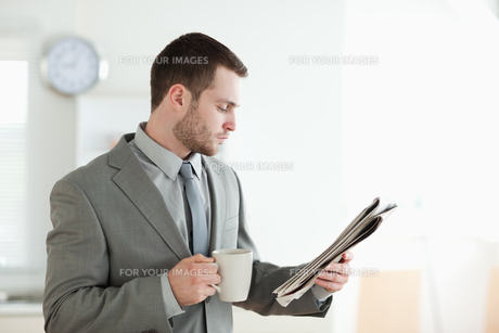 Businessman drinking tea while reading the newsの素材 [FYI00484827]
