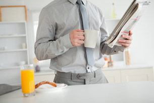 Businessman holding a newspaper while having breakfastの素材 [FYI00484836]