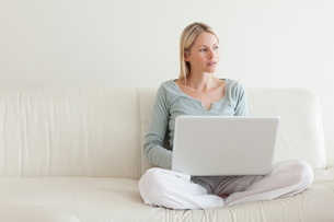 Woman sitting cross legged on the couch with her laptopの写真素材 [FYI00484840]