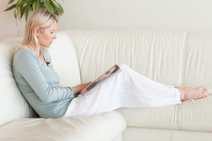 Side view of woman looking at catalog on the sofaの写真素材 [FYI00484841]