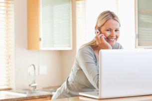 Smiling woman on the phone looking at her laptopの写真素材 [FYI00484848]
