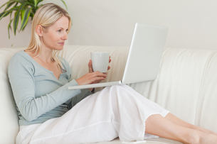 Woman sitting on the couch with a cup of coffee and her laptopの写真素材 [FYI00484849]