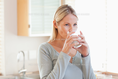 Woman in the kitchen drinking waterの写真素材 [FYI00484854]