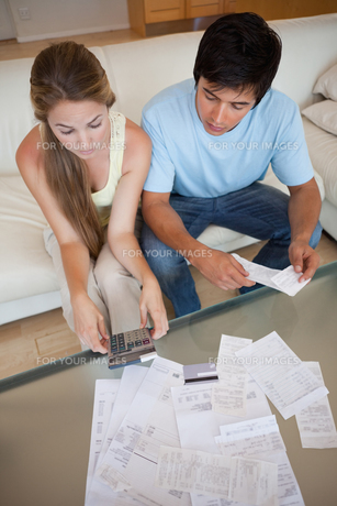 Portrait of a young couple looking at their billsの写真素材 [FYI00484861]