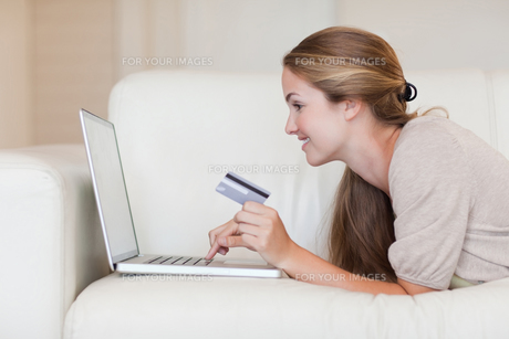 Side view of woman on the sofa shopping onlineの写真素材 [FYI00484867]