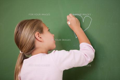 Schoolgirl drawing a heartの写真素材 [FYI00484872]