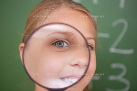 Close up of a schoolgirl looking through a magnifying glassの写真素材 [FYI00484873]