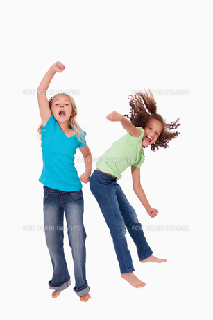 Portrait of cheerful girls jumpingの写真素材 [FYI00484879]