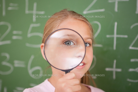 Cute schoolgirl looking through a magnifying glassの写真素材 [FYI00484881]