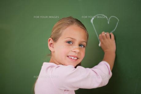 Smiling schoolgirl drawing a heartの写真素材 [FYI00484886]