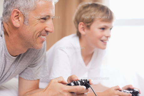 Father and his son playing video gamesの素材 [FYI00484891]