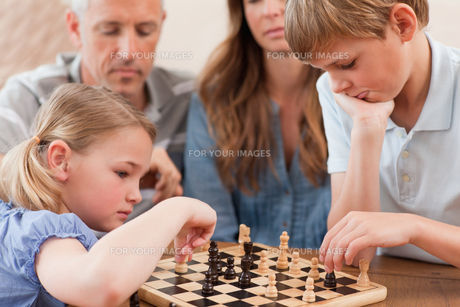 Focused siblings playing chess in front of their parentsの素材 [FYI00484893]