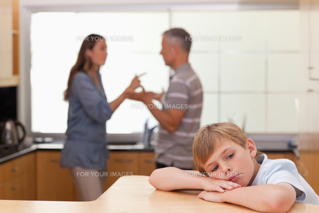 Sad little boy hearing his parents arguingの写真素材 [FYI00484895]