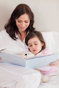 Portrait of a mother reading a story to her daughterの写真素材 [FYI00484904]